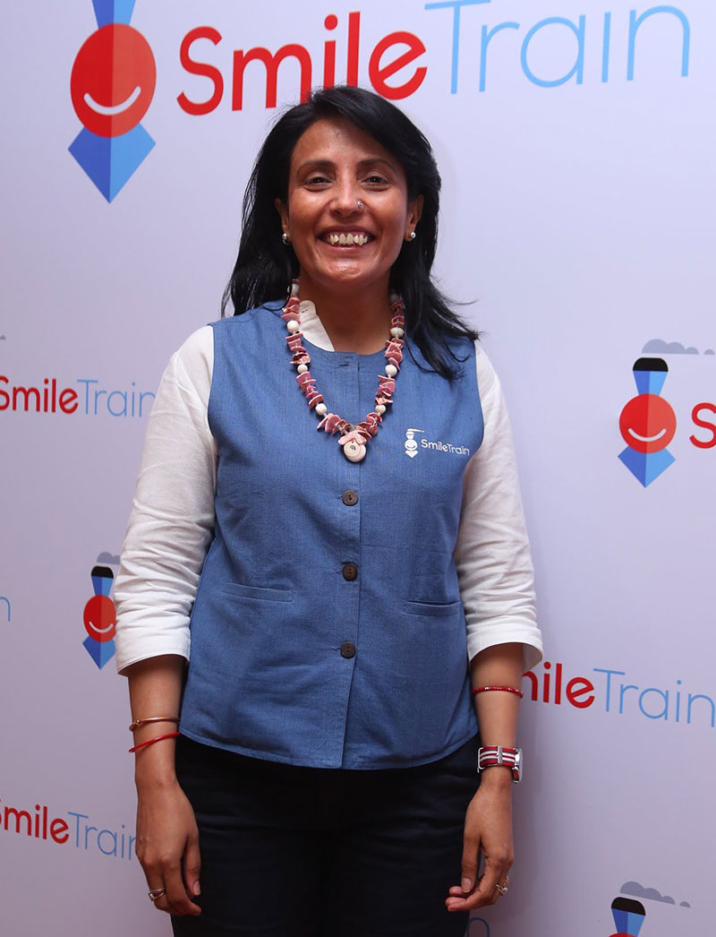 Headshot of Mamta in front of a Smile Train backdrop